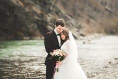 Couples heureux de mariage, jeunes mariés posant la rivière ordonnée contre le contexte des montagnes Images stock