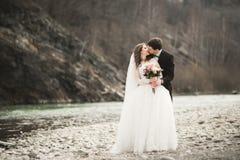 Couples heureux de mariage, jeunes mariés posant la rivière ordonnée contre le contexte des montagnes Photos stock