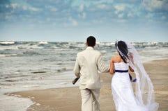 Couples heureux de mariage marchant le long du bord de la mer Image stock