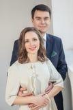 Couples heureux de mariage posant dans la chambre lumineuse s'embrassant Image stock
