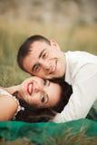 Couples heureux de mariage se trouvant sur l'herbe verte à l'heure d'été Photo libre de droits