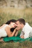 Couples heureux de mariage se trouvant sur l'herbe verte à l'heure d'été Photos libres de droits