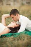Couples heureux de mariage se trouvant sur l'herbe verte à l'heure d'été Photographie stock