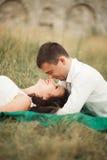 Couples heureux de mariage se trouvant sur l'herbe verte à l'heure d'été Images libres de droits