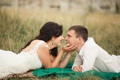 Couples heureux de mariage se trouvant sur l'herbe verte à l'heure d'été Images stock