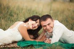 Couples heureux de mariage se trouvant sur l'herbe verte à l'heure d'été Photographie stock libre de droits