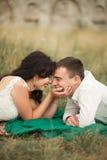 Couples heureux de mariage se trouvant sur l'herbe verte à l'heure d'été Photo stock