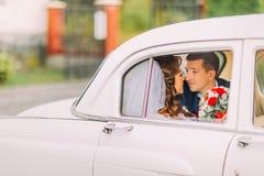 Couples heureux de nouveaux mariés embrassant sur une banquette arrière de voiture de vintage Images stock