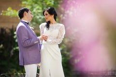 Couples heureux de nouveaux mariés, jeunes mariés tenant des mains en parc Photos stock
