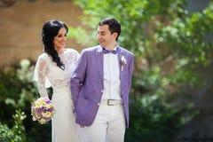 Couples heureux de nouveaux mariés, jeunes mariés tenant des mains en parc Photographie stock