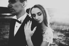Couples heureux de nouveaux mariés posant et souriant dans la robe et le costume de mariage extérieurs, noir et blanc Photographie stock