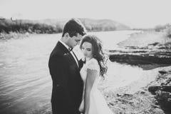Couples heureux de nouveaux mariés posant et souriant dans la robe et le costume de mariage extérieurs, noir et blanc Image libre de droits
