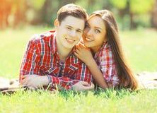 Couples heureux de portrait jeunes ayant le mensonge de sourire d'amusement sur l'herbe Images stock