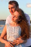 Couples heureux de portrait jeunes détendant sur la plage au coucher du soleil famille Photographie stock libre de droits