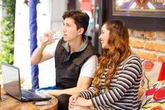 Couples heureux de sourire à la barre passant le temps ensemble, homme buvant une bouteille de l'eau tandis que son amie regarde Images libres de droits