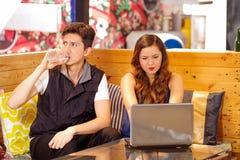 Couples heureux de sourire à la barre passant le temps ensemble, homme buvant une bouteille de l'eau tandis que son amie travaill Photo stock