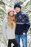 Couples heureux de sourire en forêt et chutes de neige d'hiver Image stock