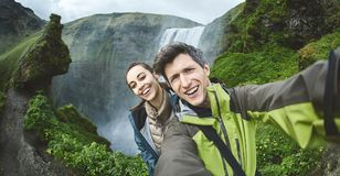 Couples heureux de sourire faisant le selfie sur un fond de cascade de Skogafoss Images stock