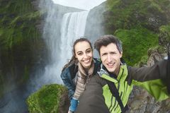 Couples heureux de sourire faisant le selfie sur un fond de cascade de Skogafoss Photographie stock