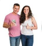 Couples heureux de sourire tenant l'argent d'argent liquide du dollar image stock