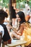 Couples heureux de tennage passant le temps au caf? photographie stock libre de droits