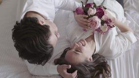 Couples heureux de tir aérien jeunes se trouvant sur le lit parlant, plan rapproché de sourire de bouquet de participation de fem clips vidéos
