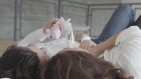 Couples heureux de tir aérien se situant dans le lit jouant avec le plan rapproché du pointe des enfants roses Jeune famille a de banque de vidéos