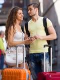 Couples heureux de voyageurs trouvant le chemin avec le téléphone Image stock