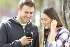 Couples heureux des adolescents partageant la musique Photos libres de droits