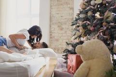 Couples heureux des amants s'asseyant sur le lit Intérieur de Noël Amoureux ensemble Image stock