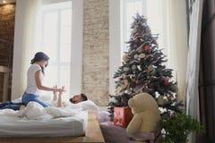 Couples heureux des amants s'asseyant sur le lit Intérieur de Noël Amoureux ensemble Photos stock