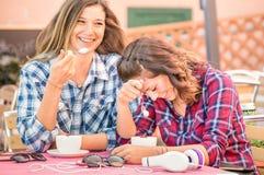 Couples heureux des amies buvant du cappuccino et ayant l'amusement Photos stock