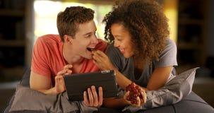 Couples heureux des amis multiraciaux à l'aide du dispositif tenu dans la main de comprimé Photo libre de droits