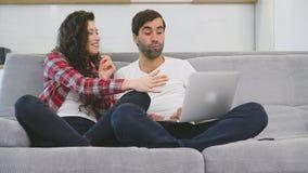 Couples heureux des milliers de plaisanteries riantes avec un ordinateur portable ensemble sur le sofa de cuisine, la jeune fille banque de vidéos