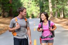 Couples heureux des randonneurs trimardant en nature Images libres de droits