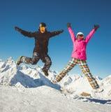 Couples heureux des surfeurs sautant dans les montagnes alpines Image stock