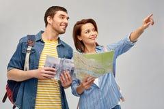 Couples heureux des touristes avec le guide et la carte de ville photos libres de droits