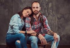 Couples heureux des touristes avec le sac à dos et la carte, caressant tout en se reposant sur un banc dans un studio Images stock