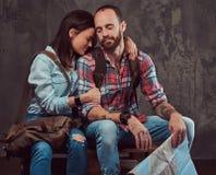 Couples heureux des touristes avec le sac à dos et la carte, caressant tout en se reposant sur un banc dans un studio Image libre de droits