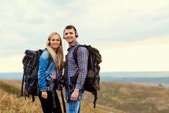 Couples heureux des touristes dans des écouteurs sur la nature Photographie stock libre de droits