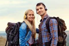Couples heureux des touristes dans des écouteurs sur la nature Photographie stock