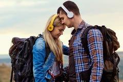 Couples heureux des touristes dans des écouteurs sur la nature Image libre de droits