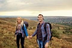 Couples heureux des touristes dans des écouteurs sur la nature Photo libre de droits