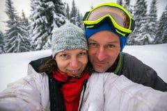 Couples heureux des voyageurs prenant le selfie dans les montagnes d'hiver Photographie stock libre de droits
