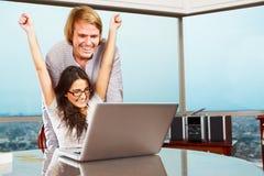 Couples heureux devant l'ordinateur portatif Images stock