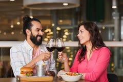 Couples heureux dinant et vin de boissons au restaurant Image stock