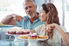 Couples heureux dirigeant des gâteaux Images libres de droits