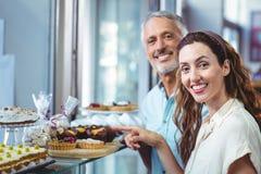 Couples heureux dirigeant des pâtisseries Image libre de droits
