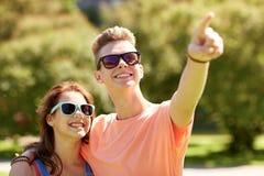 Couples heureux dirigeant le doigt au parc d'été Image stock