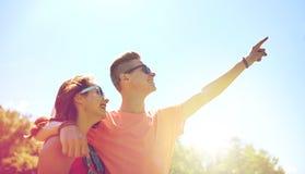 Couples heureux dirigeant le doigt au parc d'été Images stock
